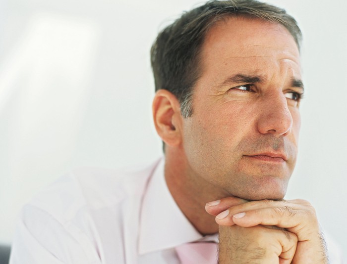 mature man thinking with chin resting on hands
