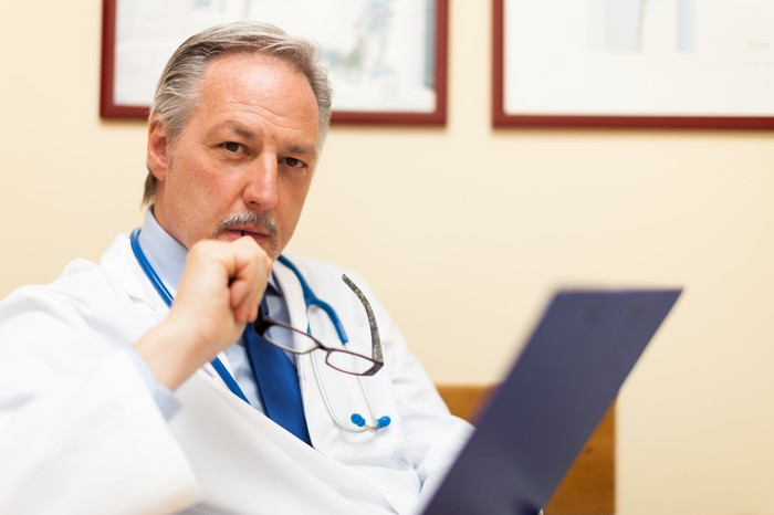 A doctor pondering what he's just read on a clipboard.
