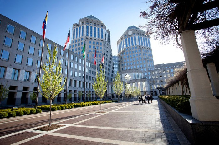Picture of entrance to P&G's corporate worldwide headquarters, with trees, flags, and small hedges in the foreground.