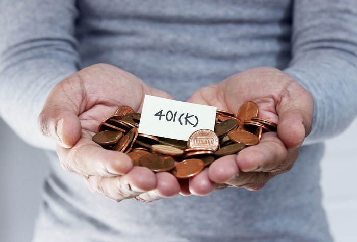 """Person holding pennies with a sign that reads """"401K"""" on top."""