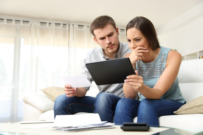 Couple looking at tablet PC with worried expressions.