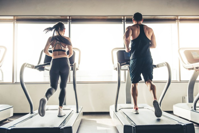 Woman and man running on a treadmill in a fitness gym