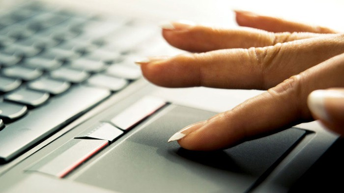 A hand using a Synaptics touchpad on a laptop.