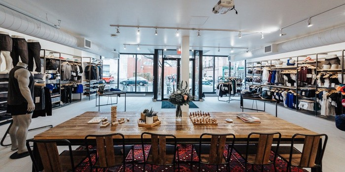 Inside a Lululemon store with a table and chairs in the foreground and merchandise on shelves to the left and right side.