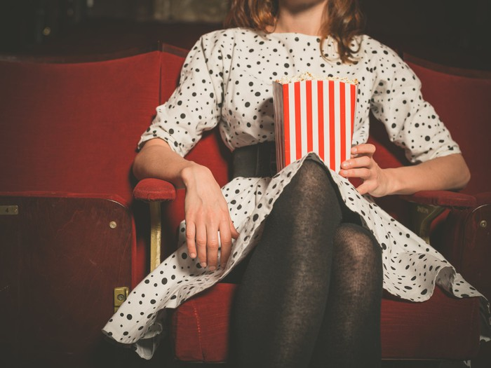 A woman sitting in a theater holding a red and white striped bag