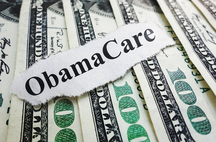 """A piece of paper that reads """"Obamacare"""" lying atop a stack of hundred dollar bills."""