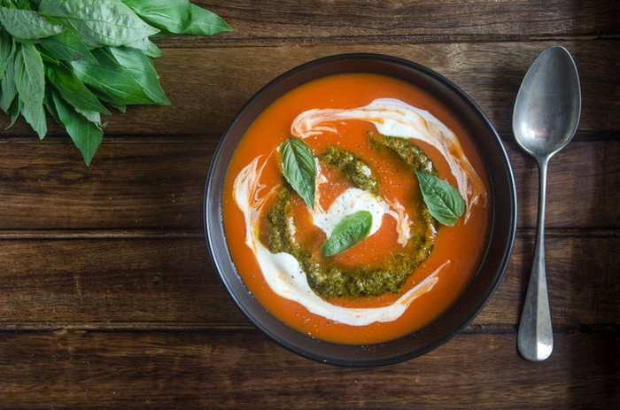 Bowl of tomato soup on wooden table, with swirls of pesto and sour cream on surface, sprinkled with fresh basil leaves