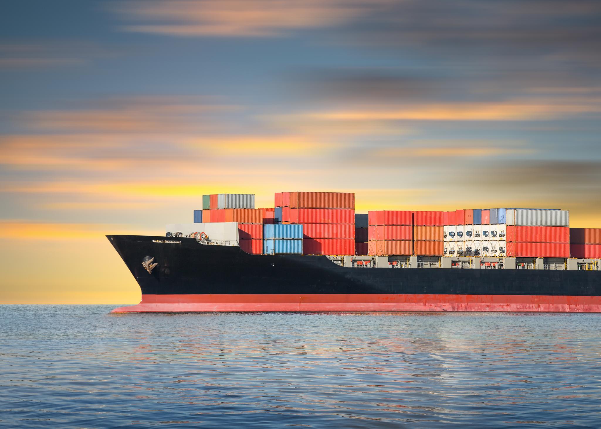 Cargo ship sailing in ocean at dawn or dusk.