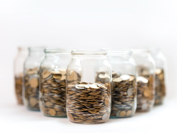 7 glass jars filled with money coins savings diversification