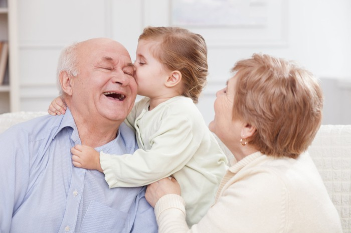 Young child kissing elderly male on forehead while elderly female looks on.