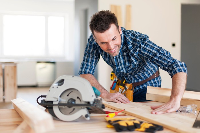 A man wearing a tool belt is measuring a piece of lumber before he cuts it.
