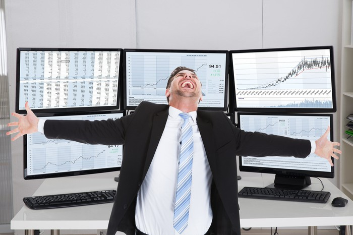 Super happy investor standing in front of monitors displaying upward rising charts.