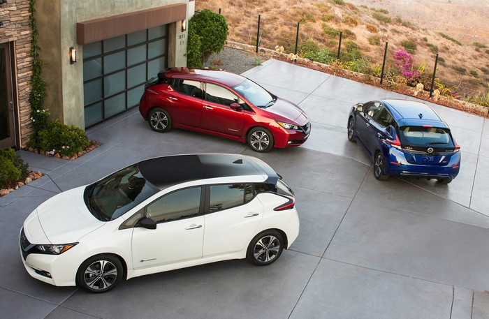 Three 2018 Nissan Leafs -- red, white, and blue -- in a suburban driveway.