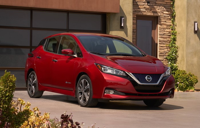 A red 2018 Nissan Leaf in a suburban driveway.