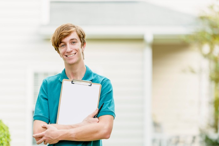A smiling man stands outside a house, clutching a clipboard.