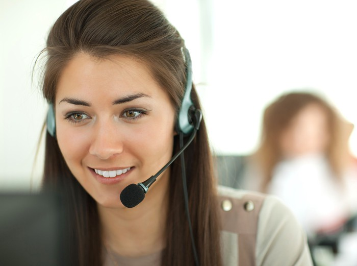 A smiling woman in an office setting wears a telephone headset.