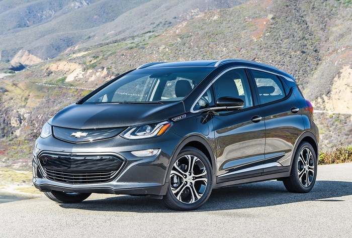 A Black 2017 Chevrolet Bolt Ev Parked Outside On Sunny Day With Mountains In The