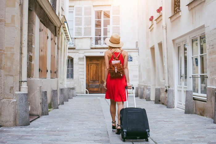 Woman in a red dress walking with a rolling suitcase.