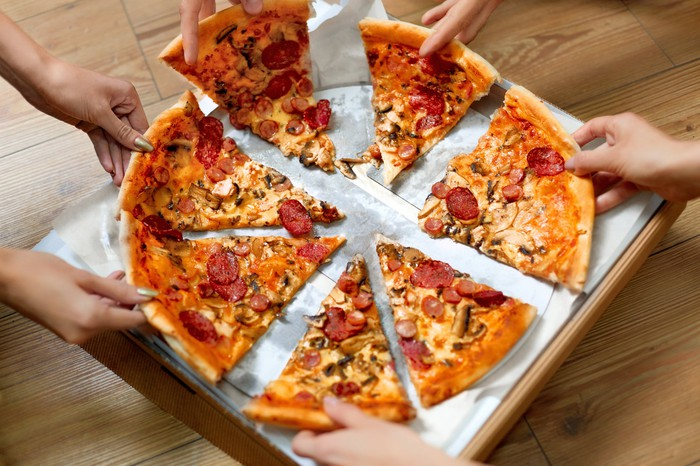 Pizza being taken from a pizza box.