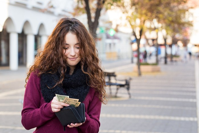 Woman pulling cash from her wallet