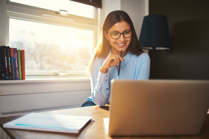 Woman with glasses looking at a laptop