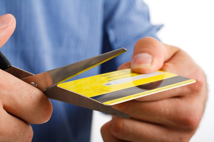 close up of two hands holding and cutting a credit card, with scissors