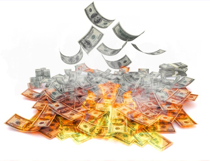 A pile of hundred-dollar bills, on fire.