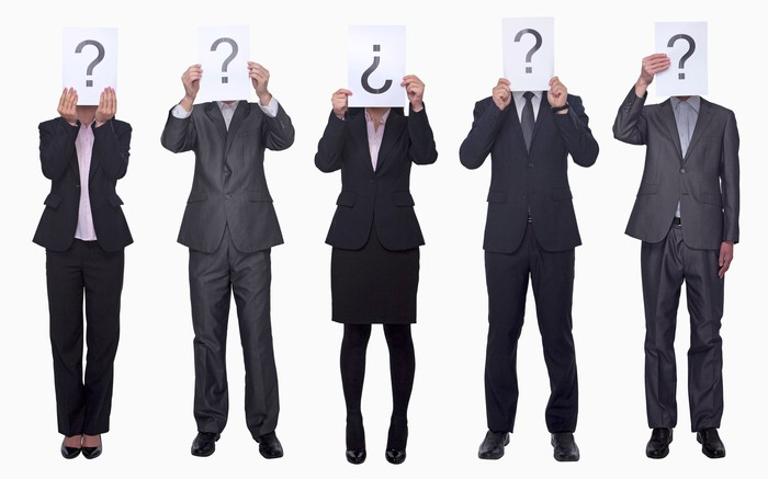 Five people dressed in business attire holding signs with question marks over their faces