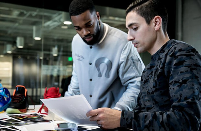 Two Under Armour employees review a document.