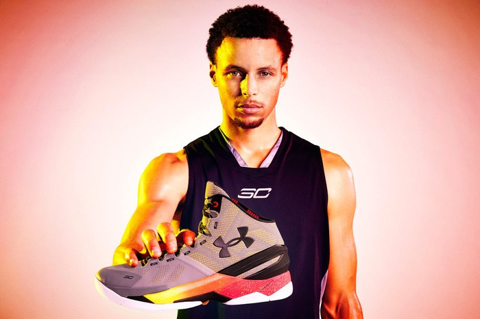 Stephen Curry holding one of his signature Under Armour shoes