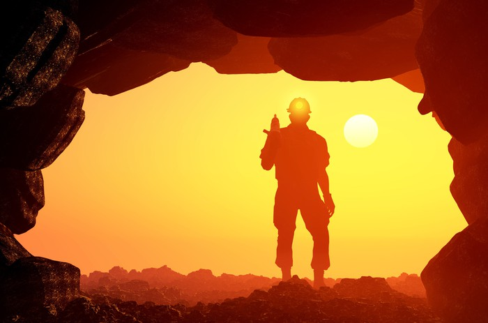 A miner standing at the mouth of a mine with the sun setting in the distance.