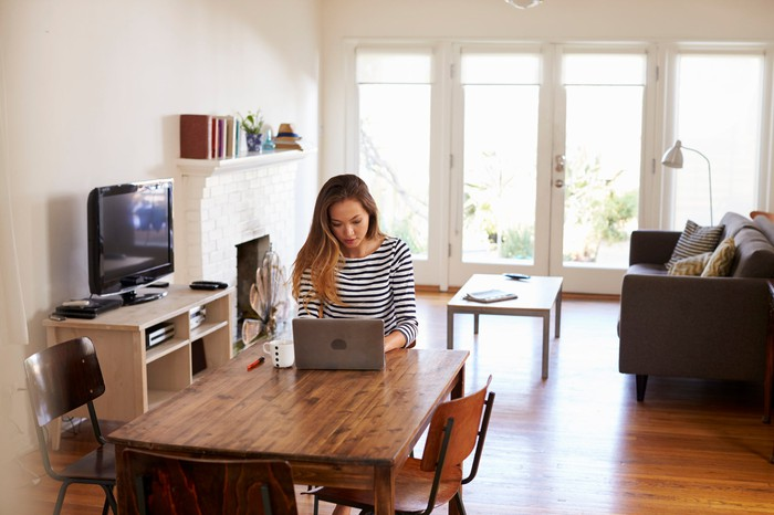A woman sits at a table in her home, working on a laptop.