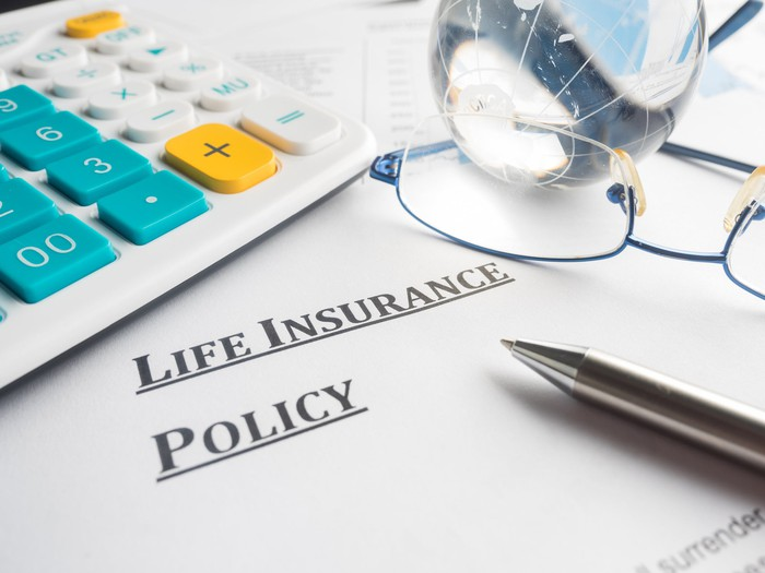 A life insurance policy with a pen and pair of eyeglasses on top of it