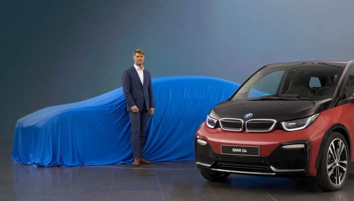Krueger is standing in front of a low-slung car covered with a blue cloth. A BMW i3 hatchback is parked next to him.