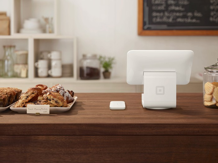 Square's physical payments system installed at a retail store, sitting on a counter between a variety of sweet baked goods.