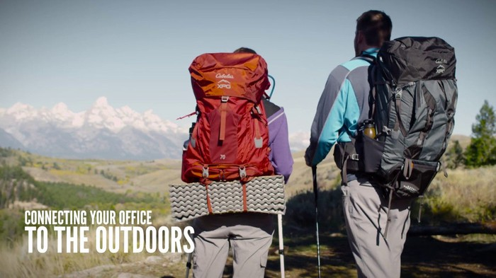 Two people with backpacks looking at a mountain range.
