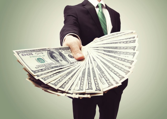 A man in a suit holding fanned-out hundred-dollar bills.
