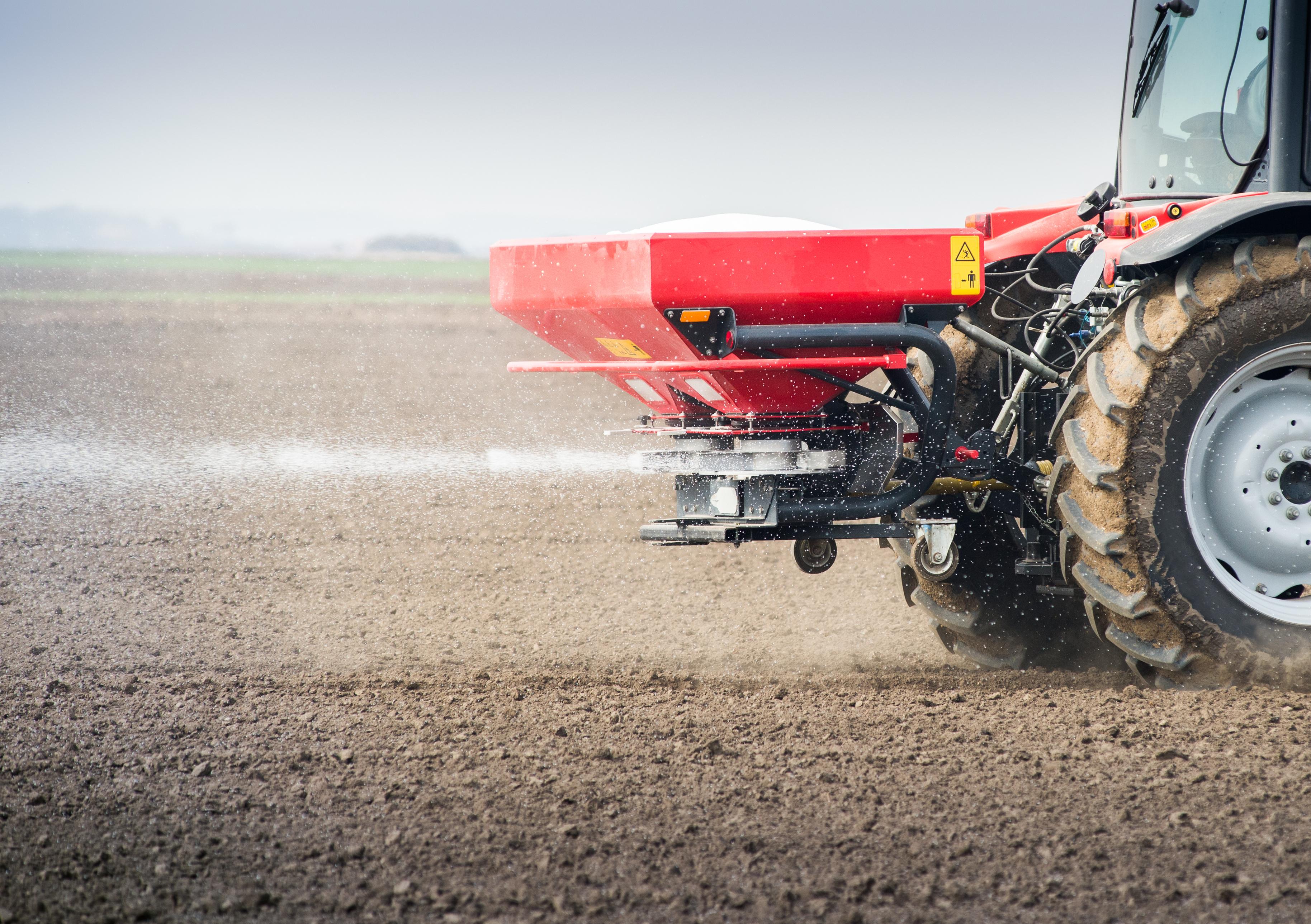 A tractor on a farm applying fertilizer to a field.