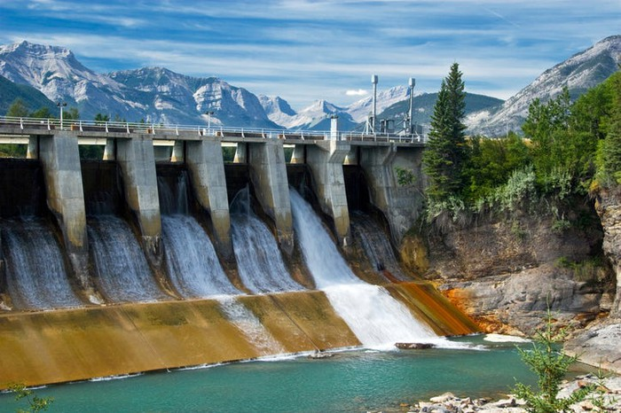Hydroelectric dam with mountains in the distance.