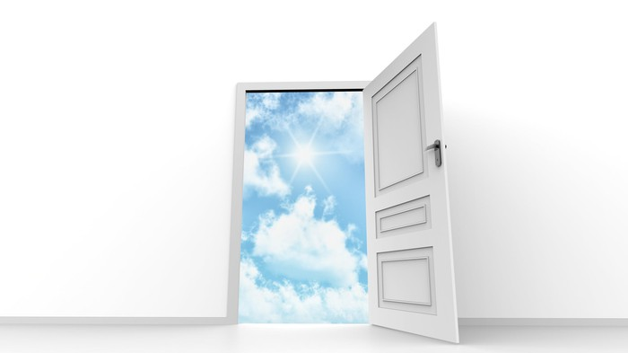 Door open with blue sky and sun shining through clouds