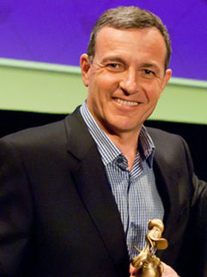Disney CEO Bob Iger, smiling and holding a gilded Donald Duck statuette.