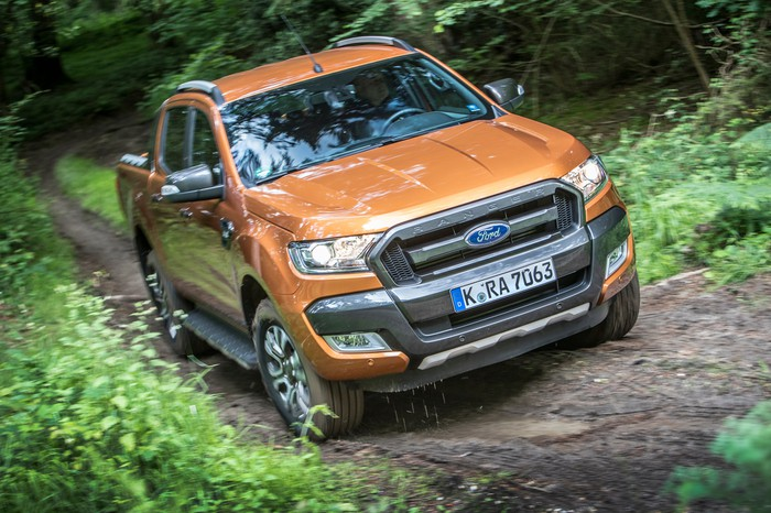 An orange 2017 Ford Ranger pickup on a dirt road in a forest, wth a European license plate.