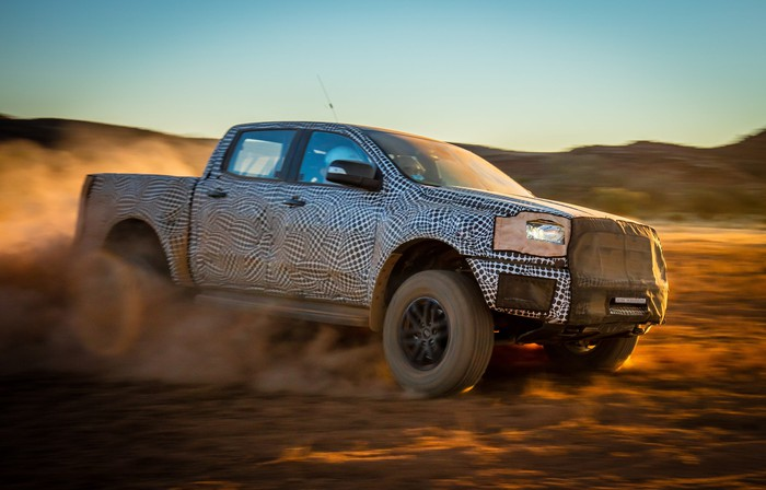 A prototype Ford Ranger Raptor, partly covered to hide its styling details, is shown moving at high speed across a desert landscape in Australia.