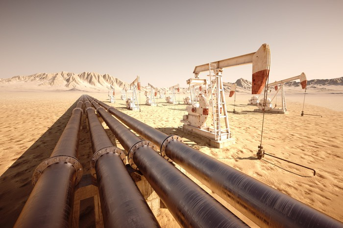 Pipelines and oil pumps in a desert landscape with mountains in background.