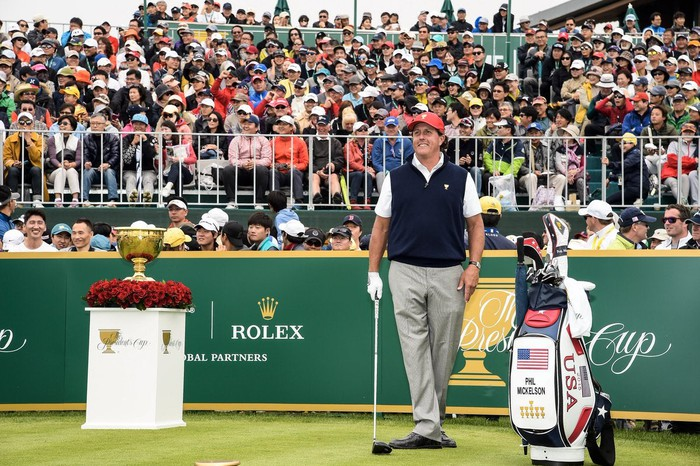 Phil Mickelson stands holding a club in front of fans in bleachers.