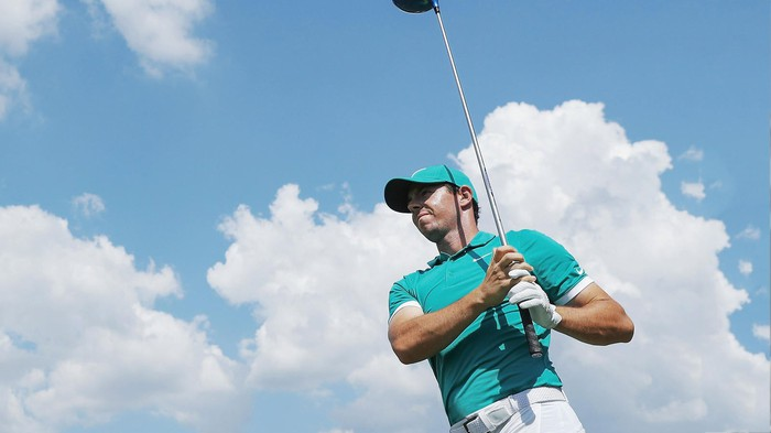 Rory McIlroy holds a golf club in front of him with the sky as a background.