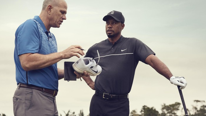 Tiger Woods leans on a golf club and talks with a man holding a Nike shoe.