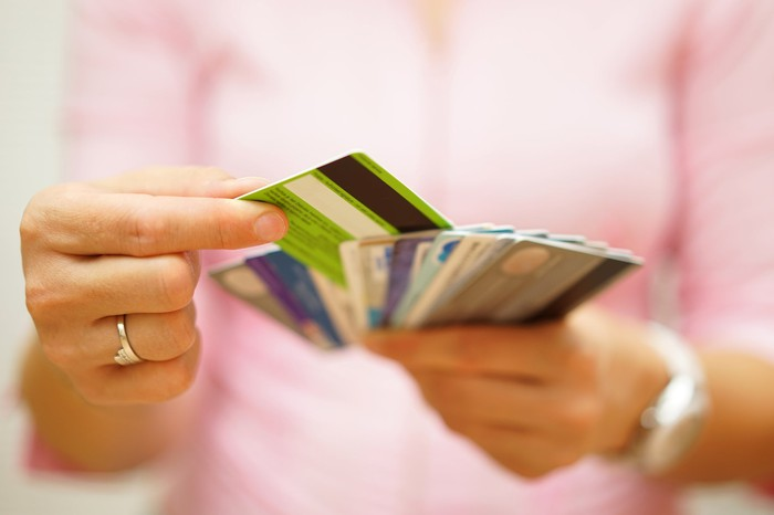 blurry torso of woman in pink shirt - we see her hands holding credit cards fanned out and she's selecting one of them