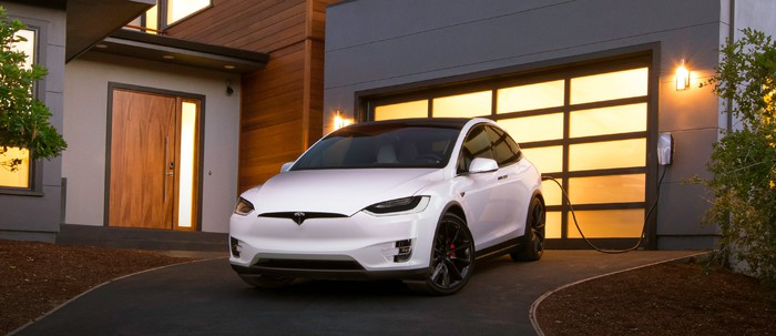 A white Tesla Model X charging at home in a driveway.
