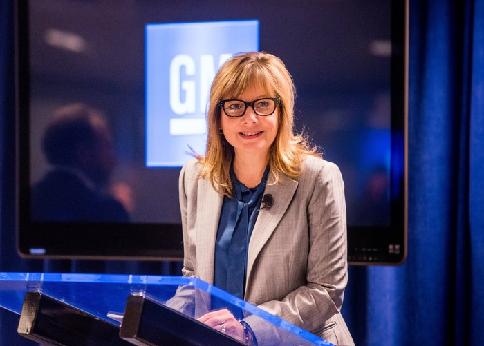 Mary Barra is shown standing at a podium in front of a lighted GM logo.